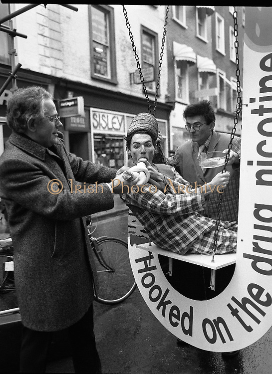 """Anti-smoking Campaign..1986..12.03.1986..03.12.1986..12th March 1986..In Grafton Street,Dublin,the anti-smoking campaign """"Unhooked A Cigarette Addict""""from thre perils of smoking. Today,Wednesday,was declared 'National No Smoking Day""""in order to heighten awareness...Pictured in Grafton,Street,Dublin,Mr Donal O'Shea,Chairman of the Health Education Bureau,in conjunction with students from The College Of Marketing and Design highlight the dangers of smoking.The students distributed fruit to passers by to give a healthy option to smoking...Note. Through the years Medical Science has determined that smoking is a major contributory factor in cancer and heart disease. With further research """"Passive smoking""""(that is those in the vicinity of smokers but who do not smoke themselves) was also found to be detrimental to health..In March 2004 Ireland became the first country in the World to introduce a ban on smoking in the workplace,This included pubs,cinemas and public transport etc..In 2012 the anti smoking lobby is pushing for a complete ban on smoking in all public spaces and within the confines of private cars.."""