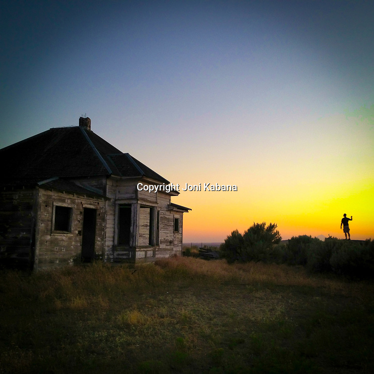 Photographer Alan Thornton watches the sun set near an abandoned house near Condon, Oregon (iPhone image)