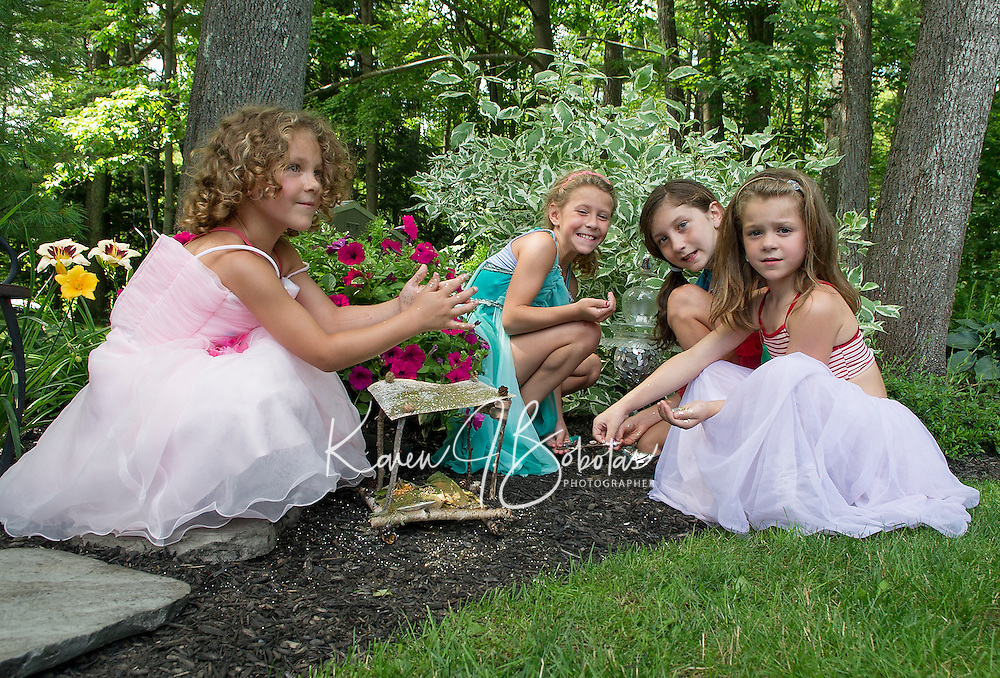 """Fairies"" from the Boys and Girls Club add sparkle to their fairy houses placed among the gardens at Robert King and Elaine Muller's home prior to Opechee Garden Club's ""Awesome Blossoms"" Tour on Saturday.  (Karen Bobotas/for the Laconia Daily Sun)"