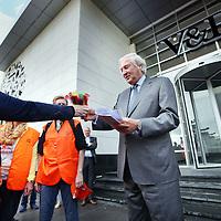 """Nederland, Amsterdam Z.O. , 13 augustus 2013.<br /> Overhandiging petitie werknemers distributiecentrum Aduard aan directie V&D.<br />  Ca. 50 werknemers van V&D distributiecentrum Aduard (Groningen), enkele werknemers van V&D-filialen, Toon Wennekers, coördinator arbeidsvoorwaardenbeleid FNV Bondgenoten en FNV Bondgenoten <br /> Overhandiging petitie en veren aan de V&D-directie voor fatsoenlijk sociaal plan. Werknemers V&D willen een goed sociaal plan, geen veren Circa 50 werknemers van het V&D-distributiecentrum in Aduard reizen dinsdagochtend naar Amsterdam waar zij rond 11.00 uur een petitie voor een fatsoenlijk sociaal plan aan de V&D-directie overhandigen. Het ultimatum dat zij V&D stelden, liep maandagmiddag af zonder enige handreiking van V&D. Toon Wennekers, coördinator arbeidsvoorwaardenbeleid bij FNV Bondgenoten, steunt de werknemers en is bij de overhandiging aanwezig. """"We willen geen veren, we willen een fatsoenlijke ontslagvergoeding"""" """"Jarenlang kregen we veren in onze kont gestoken maar nu V&D van ons af wil, worden we met een fooitje afgescheept"""", aldus een werknemer<br /> Op de foto CEO topman V&D dhr. Jacob de Jonge wordt de petitie en veren aangeboden.<br /> Foto:Jean-Pierre Jans"""