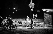 The parking lot at the Town and Country Motel serves as the playground for the dozen plus kids who live in the motel rooms with their parents. The six kids of Cora McNeil and Mike Jackson ride bikes, play basketball and chase dogs into the evening hours. (Mike Fender Photo) w/ story