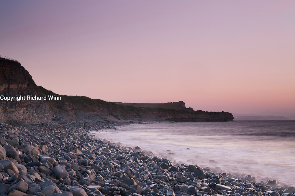 Pastel pinks and purples after the sun has set at Kilve Beach, with waves washing over the loose rocks.