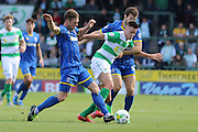 Jon Meades of AFC Wimbledon and Dannie Bulman of AFC Wimbledon stop Harry Cornick during the Sky Bet League 2 match between Yeovil Town and AFC Wimbledon at Huish Park, Yeovil, England on 12 September 2015. Photo by Stuart Butcher.