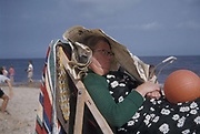 Woman fast asleep on a deckchair at the beach, sheltering under a newspaper, Gorleston Beach, Norfolk, 1957