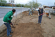 Earthworks workshop participants shaping water harvesting basins in Bonnie's front yard.