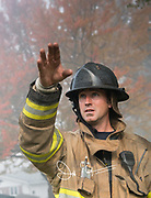 A firefighter points with his hand through smoke filled air.