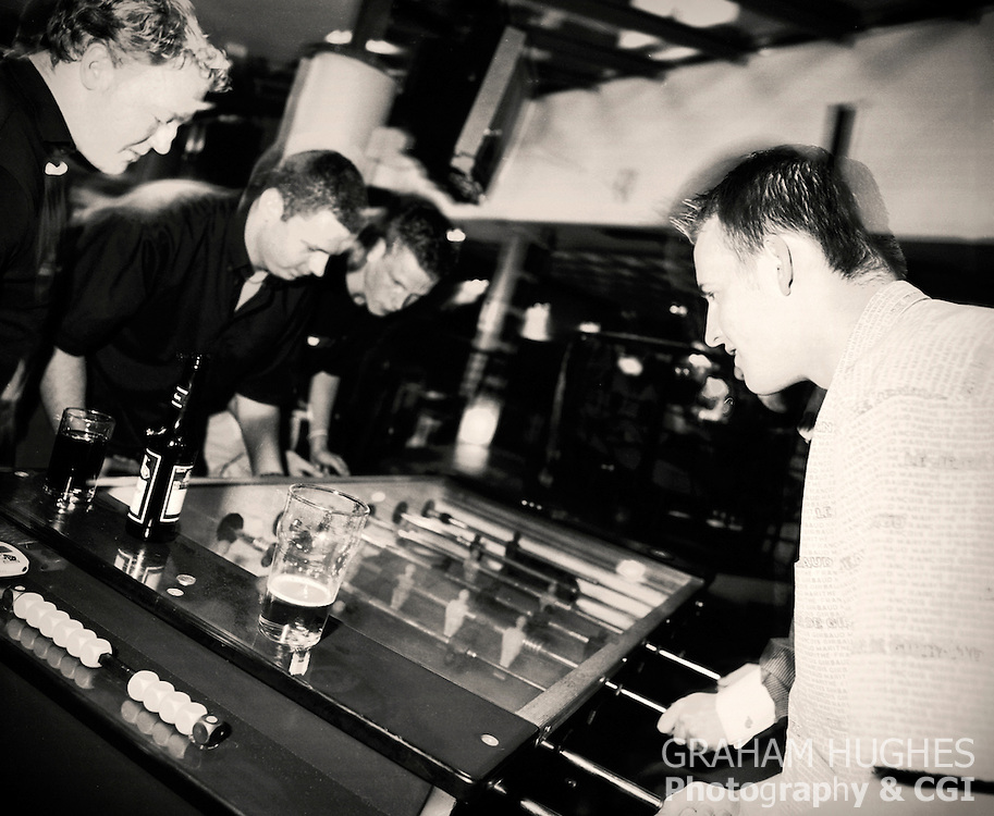 Students playing on Foos Ball table in St Andrews student union bar.