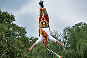 A Volador performs the sacred ceremonial Dance of the Voladores in the Parque Takilhsukut at the pre-Columbian archeological complex of El Tajin in Tajin, Veracruz, Mexico. The Danza de los Voladores is a indigenous Totonac ceremony involving five participants who climb a thirty-meter pole. Four of these tie ropes around their waists and wind the other end around the top of the pole in order to descend to the ground. The fifth participant stays at the top of the pole, playing a flute and a small drum. The ceremony has been inscribed as a Masterpiece of the Oral and Intangible Heritage of Humanity by UNESCO.