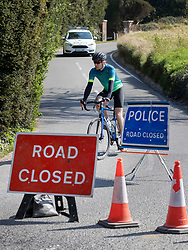 © Licensed to London News Pictures. 10/04/2020. Dorking, UK. A cyclists leaves a closed road at Surrey beauty spot Box Hill near Dorking after being turned back by police. Police have closed Box Hill over the Easter Weekend to stop the spread of the coronavirus . The government has warned that people must continue to follow the public health guidance over the Easter weekend. Photo credit: Peter Macdiarmid/LNP