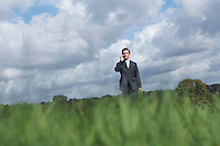 Business man talking on mobile phone in field selective focus