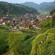 Overview of a remote mountain village in China. <br /> <br /> Shielded from the rest of Chinese civilization by a cascade of steep mountains, this village and the other surrounding lush villages have kept their Dong minority traditions and arts from centuries ago.<br /><br />With a history that goes back to the Tang dynasty, the area is adorned with stunning wooden Flower Bridges, bell towers and cascades of beautiful old houses. The Dong people have no written language, but use fine embroidery to communicate their love.<br /><br />Yet, as highways and tunnels plough through these mountains, the future of the village&rsquo;s 525 households is at crossroads. There is already a government blueprint to turn Dimen into a satellite town in the coming three years, as China embarks on its latest urbanization drive.