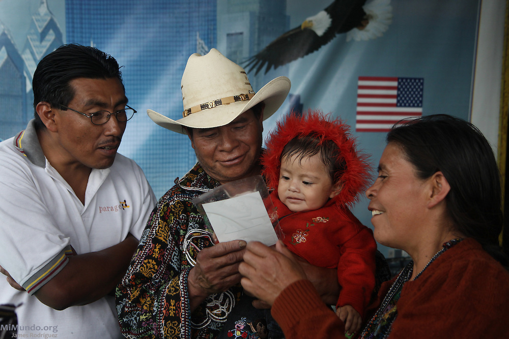 A Kaqchikel Mayan family from Solola looks at a photograph taken in Guatemala City's central park at a street photo stand featuring a U.S. flag, a bald eagle and skyscrapers. Backgrounds with U.S. motifs are very common in Guatemala as there are thousands of Guatemalan immigrants in the U.S. who send back very important remittances for their loved ones back home. Guatemala City, Guatemala. July 10, 2011.