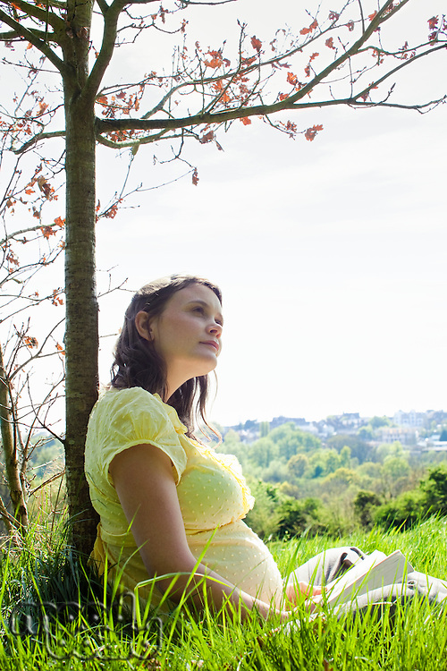 Pregnant woman sitting on grass
