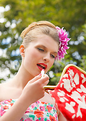 Close up of a young woman applying lipstick whilst holding her handbag