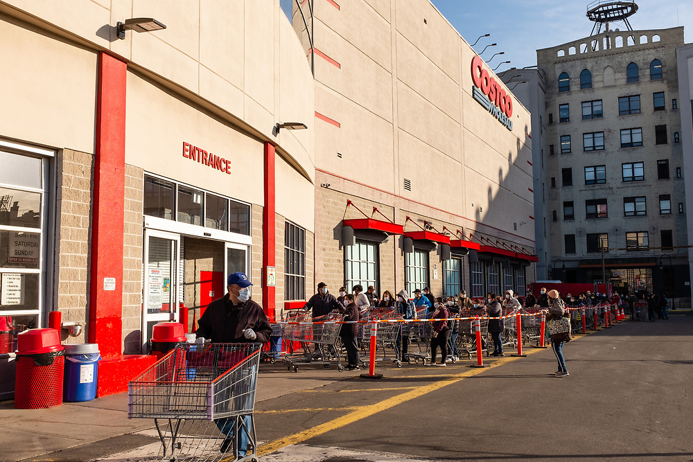 Brooklyn, NY - 7 April 2020. At 8 AM, the line to enter the grocery and warehouse store Costco on 3rd Avenue already stretches across the front of the building and along the length of the side back to 2d Avenue. The store opens from 8 to 9 AM on Tuesdays through Thursdays for customers over 60.