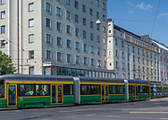 Helsinki, Finland -- July 19, 2019. A Tram goes past stores and apartment flats on a busy thoroughfare in Helsinki, Finland.