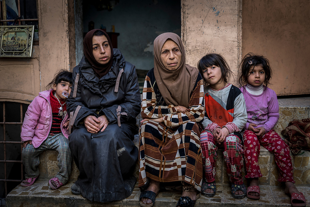 Mother of 7 Sawsan (second from left), 42, her mother Nuhad Hamdoon, 64, and her daughters sit on a step in their home in Mosul's Old City. For 7 months during the intense fighting between ISIS and Iraqi forces, the family hid inside their basement  with little access to food and clean water. On July 1, 2017, they were liberated from ISIS and fled to the east side of the city. In February this year the family were able to move back to their home in the Old City, surrounded by the ruins of their neighbours' homes that were hit by airstrikes.
