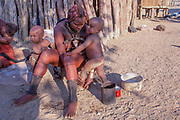 Mother and child Young Himba woman wearing headgear and decorations. The Himba are a pastoral and nomadic people of northern Namibia. They tend herds of goats and cattle in the arid desert environment, living in extended families in homesteads. Both men and women go topless. Photographed in Kaokoland, Namibia, Southern Africa.