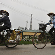 Women wearing a face-masks bicycle outside the coal-powered electricty plant in Phai Lai, about 70 kilometers east of Hanoi, Vietnam, 14 September, 2007.