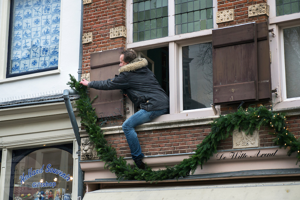 Utrecht. Man hangt kerstversiering op vanuit het raam. Oude gracht Utrecht