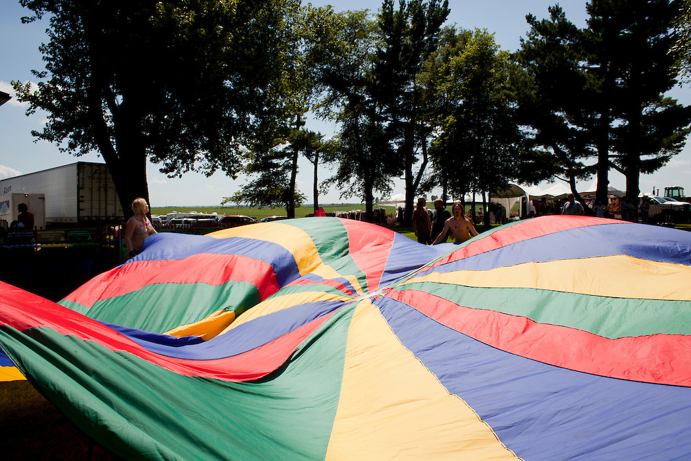 Children and adults play with a giant parachute on the lawn at Camp Euforia on Friday, July 18, 2015. Jerry Hotz has hosted the annual music fest at his farm north of Lone Tree since 2003.