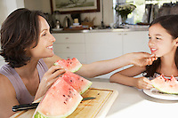 Mother and daughter eating water melon at table in kitchen