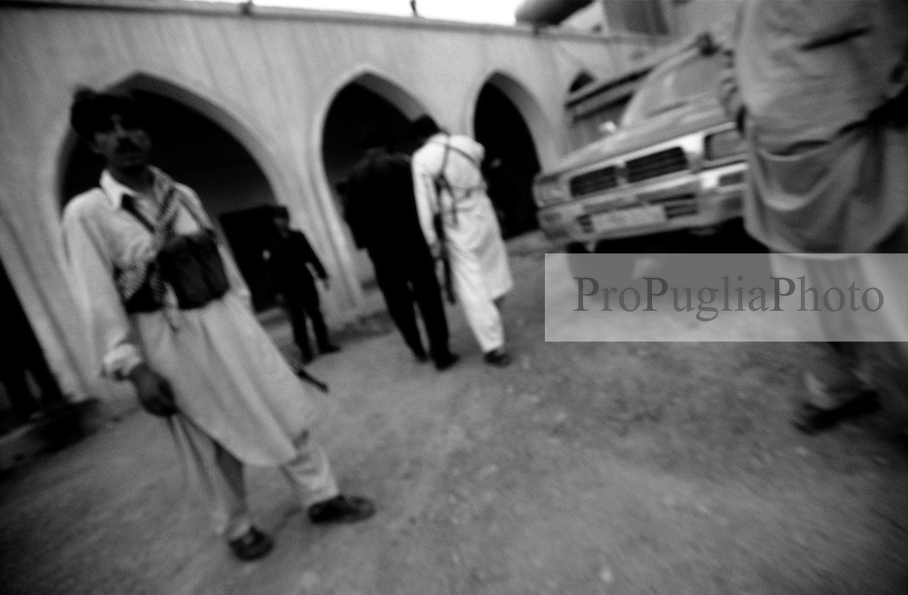 AFGHANISTAN, 10 AUGUST 2005..KHOST Police HQ..Armed policemen, wearing local dress, look at a foreigner  who has just been taken into custody for identification...After the killing of General Ahmad Shah Massoud by a group of suicide bombers in 2001, who were pretending to be journalists, it has become very difficult for the Press to work independently in Afghanistan...