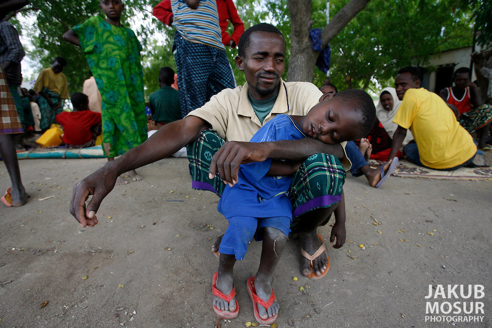 September 13, 2006 - Ibrahim Sirat Abdi and his son Deud Ibrahim Sirat, 4, of Mogadishu, wait with another 320 Somali refugees at Liboi, Kenya near the border with Somalia before being transported to Dagahaley Refugee Camp in Dadaab. Somalis are fleeing from recent clashes between Islamic Courts and the Transitional Government of Somalia and the latest drought in the region. Over 21,000 refugees since January 2006 have arrived in Dadaab, in the North Eastern province of Kenya. Despite the recent influx of refugees, funding by the international community has been reduced, according to CARE International. (Photo by Jakub Mosur/Polaris)