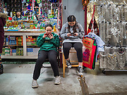 29 FEBRUARY 2020 - ST. PAUL, MINNESOTA:  Girls playing on their smart phones in front of their family's shop in the Hmong Village. Thousands of Hmong people, originally from the mountains of central Laos, settled in the Twin Cities in the late 1970s and early 1980s. Most were refugees displaced by the American war in Southeast Asia. According to the 2010 U.S. Census, there are now 66,000 ethnic Hmong in the Minneapolis-St. Paul area, making it the largest urban Hmong population in the world. Hmong Village, the largest retail and restaurant complex that serves the Hmong community, has more than 250 shops and 17 restaurants.   PHOTO BY JACK KURTZ