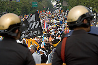 "BANGKOK, THAILAND  -  March 14: Thai police officers look on as tens of tousands of demonstrators seeking the resignation of Prime Minister Thaksin Shinawatra marched to government house on March 14, 2006 in Bangkok, Thailand. Marching several kilometers from the Grand Palace to Government House the protesters surrounded Thaksin's office chanting ""Thaksin Get Out"", as the Prime Minister threatened a state of emergency if the demonstration turned violent.  (Photo by David Paul Morris)"