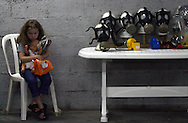 An Israeli girl holding her baby doll waits to get a gas mask at the gas mask distribution center in the Jersualem Mall Wednesday, Oct. 10, 2001. Thousands of Israelis have visited gas mask colleciton centers sinc ethe terror attacks on the United States on Sept. 11, out of concer for possible chemical attacks in response to the U.S. led offensive to Afghanistan.