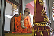 The Coolest Mummified Monk in the World<br /> <br /> The body of thailand's most famous mummified monk, Loung Pordaeng, is on display in a specially constructed building on Koh Samui island. When he died more than 20 years ago, as he was sitting in a meditation position. He is still in that same position and his body shows few signs of any major decay.<br /> Phra Khru Samathakittikhun or Loung Por Daeng was born in 1894, and was a well respected family man within the local community on Koh Samui and first become ordained as a monk when he was in his early twenties. He spent two years in Wat Samret before exiting and marrying a local lady from Lamai with whom he had six children, a few still alive on the island today.<br /> Upon reaching fifty years of age, once his children were all grown up, Loung Por Daeng, decided to dedicate the latter part of his life to Buddhism and returned to the temples where he felt so at peace. He was ordained as a monk in 1944.<br /> After living in Bangkok and studying buddhism, he decided to return to his family home, which was located just behind the current Wat Kunaram. Most famously, two months before his death, at the age of 79 years and 8 months, he requested the company of his students to inform them that he felt his death was imminent and wanted to instruct them as to his last wishes. He requested that should his body decompose that he be cremated and his ashes scattered at the famous 'Saam Jaeg' in Hua Thanon, meaning the three forked road intersection, in Thai.<br /> He went on to request that should his body not decompose, he would like to stay at the temple and be placed in an upright coffin on display as a symbol to inspire future generations to follow Buddhist teachings and be saved from suffering.<br /> In his final seven days of mortal life, he no longer spoke to anyone or ate or drank anything, concentrating solely on his mediation and the path to enlightenment. He died a week later in the same position that we can see him sitting in nowadays.<br /> He's in impeccabl