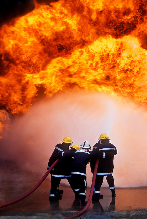 Firemen fighting a fire at an oil refinery.