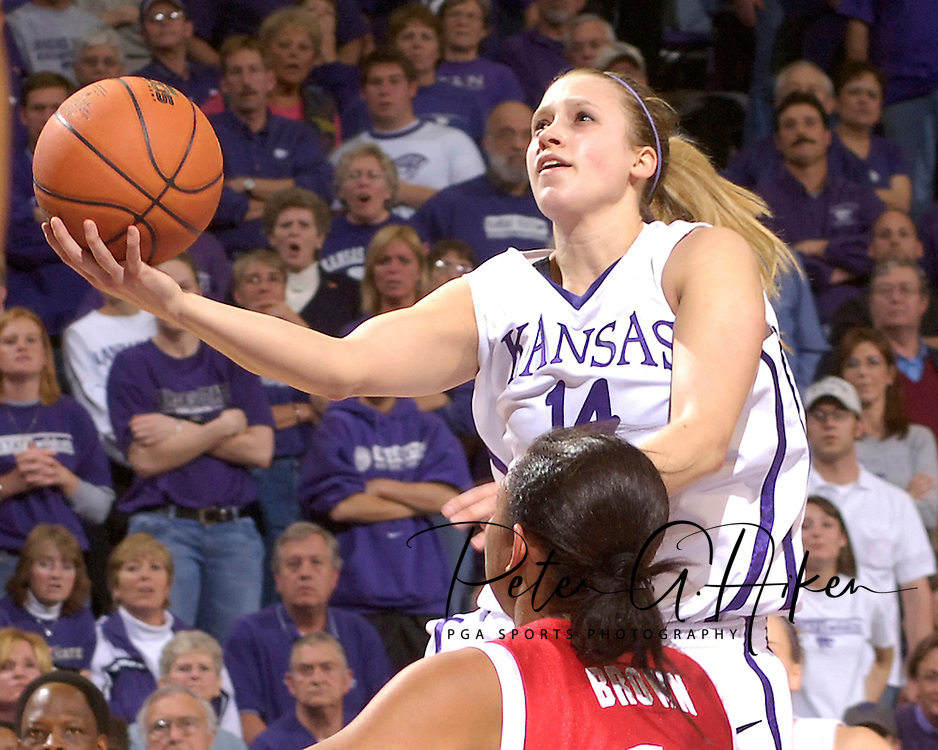 Kansas State's Claire Coggins (14) drives to the basket over Western Kentucky's Brianne Brown (front), during the second half at Bramlage Coliseum in Manhattan, Kansas, March 28, 2006.  K-State defeated Western Kentucky 57-56 in overtime of the WNIT Semifinals.