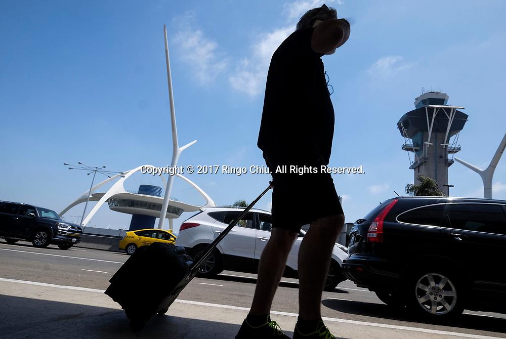 6月30日,在美国洛杉矶国际机场,一名出发旅客抵达机场前往目的地。根据南加州汽车俱乐部(Automobile Club of Southern California) 发表最新报告,在这个独立日周末期期间,全加州游旅客人数将创纪录首次超过500万人次,其中南加洲地区的游客人数也将超过310万人次。新华社发 (赵汉荣摄)<br /> A holiday traveler arrives before check in at Los Angeles International Airport on Friday, June 30, 2017 in Los Angeles, the United States. Holiday travel will increase on this Independence Day weekend when, for the first time, the number of travelers from California will exceed 5 million while those just from the Southland jumps above 3.1 million, according to the Automobile Club of Southern California.. (Xinhua/Zhao Hanrong)(Photo by Ringo Chiu)<br /> <br /> Usage Notes: This content is intended for editorial use only. For other uses, additional clearances may be required.
