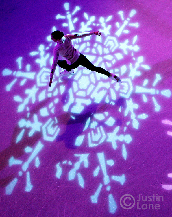 A figure skater passes through a snowflake spotlight during the 74th annual ceremony for the lighting of the Rockefeller Center Christmas tree in New York on Wednesday 29 November 2006.