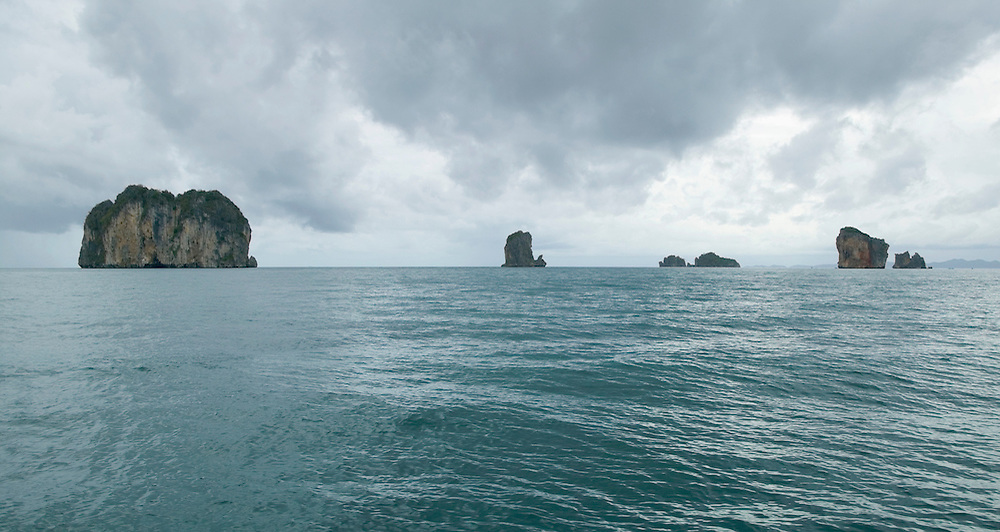 Limestone rock formations rising above the Andaman Sea Southern Thailand as a rain storm approaches&amp;#xA;<br />