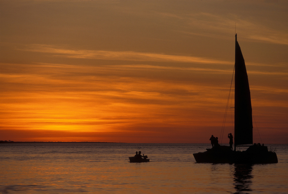 Australia, Northern Territory, Sailboat under vivid sunset off Mindal Beach in Darwin