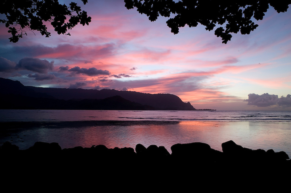 "The view of the sunset across Hanalei Bay to ""Bali Hai"" from the public beach below the Princeville Resort"