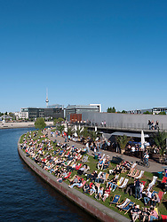 Busy waterside cafe in summer  beside Spree River in central Mitte Berlin Germany