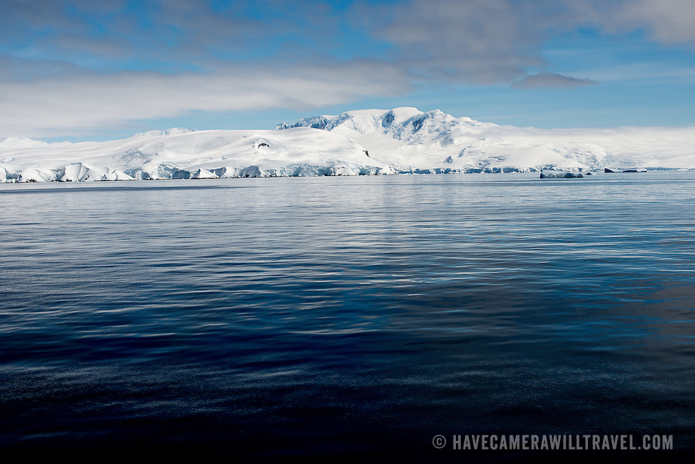 Snow and ice-covered mountains line the coast along the western side of the Antarctic Peninsula in Fournier Bay.
