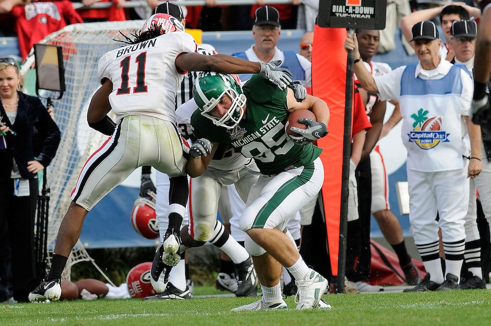 January 1, 2009: Ramarcus Brown of the Georgia Bulldogs tackles Garrett Celek of the Michigan State Spartans during the NCAA football game between the Michigan State Spartans and the Georgia Bulldogs in the Capital One Bowl. The Bulldogs defeated the Spartans 24-12.