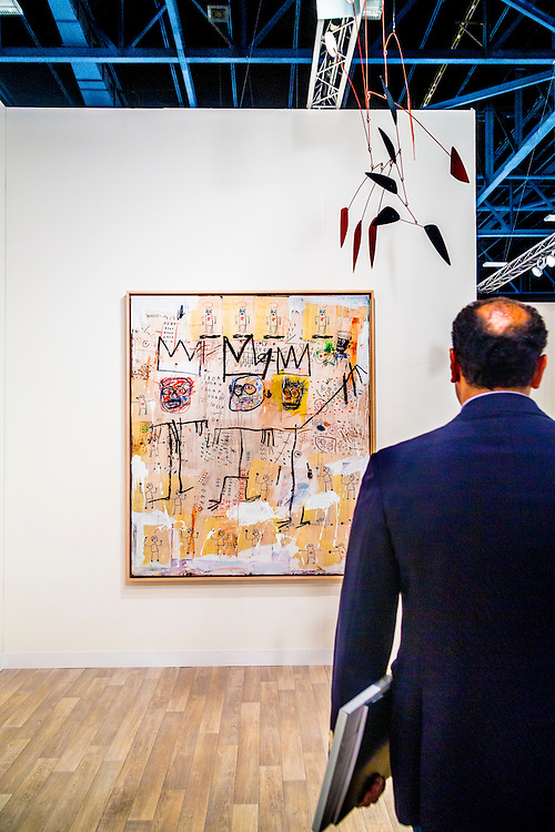 "Man views ""The Ruffians"" by Jean-Michael Basquiat, 1982, arcrylic and oil paintstick and paper, at the Kukje Gallery, Seoul/ Tiny Kim Gallery, New York, at Art Basel Miami Beach 2012"