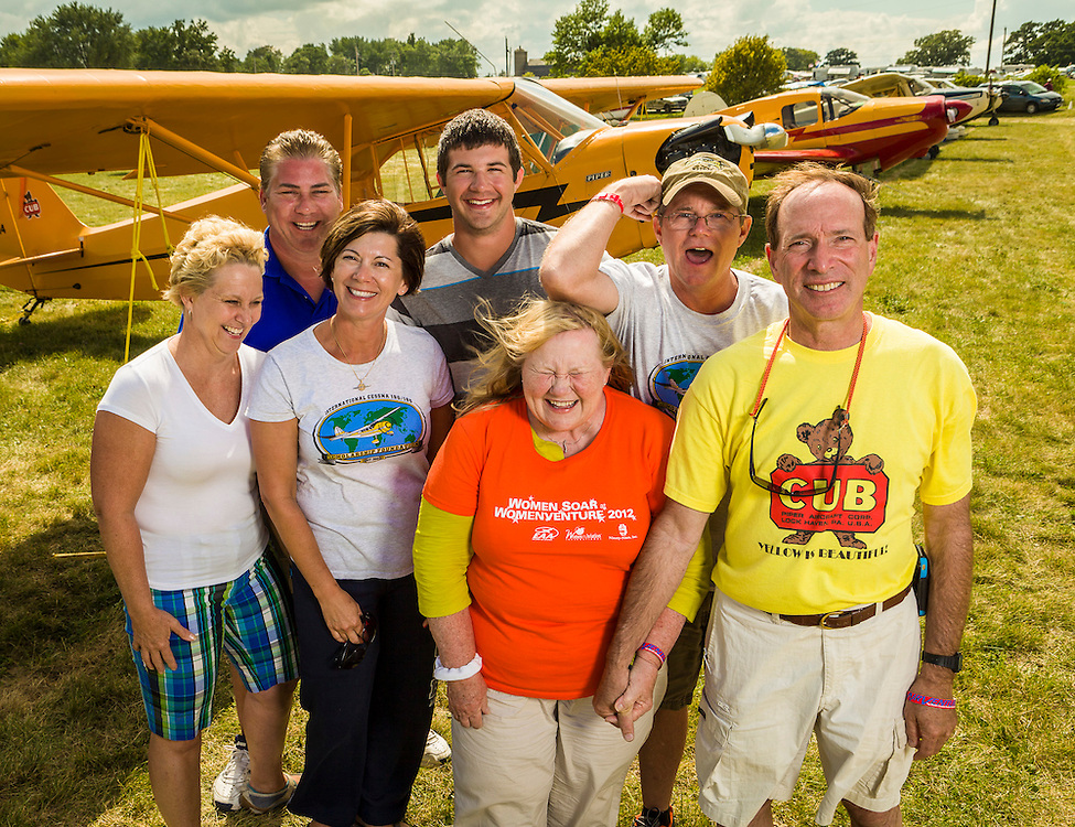 Piper Cub owners at Oshkosh, enjoying a moment of family fun during AirVenture 2012.  Oshkosh, Wisconsin.  Created by aviation photographer John Slemp of Aerographs Aviation Photography. Clients include Goodyear Aviation Tires, Phillips 66 Aviation Fuels, Smithsonian Air & Space magazine, and The Lindbergh Foundation.  Specialising in high end commercial aviation photography and the supply of aviation stock photography for commercial and marketing use.