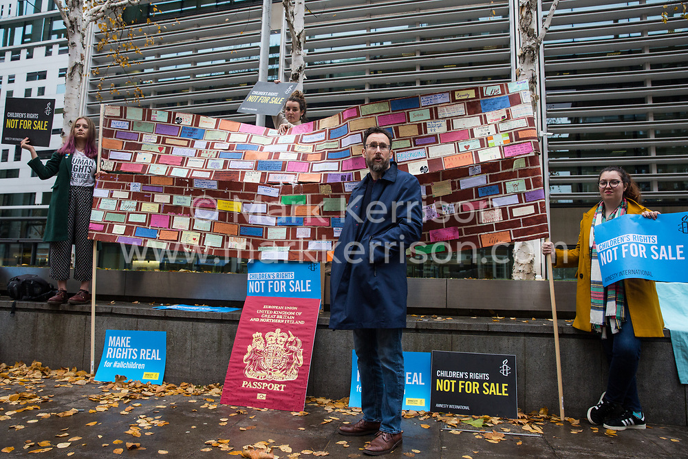 London, UK. 25 November, 2019. Steve Valdez-Symonds, Amnesty UK Refugee and Migrant Rights Programme Director, speaks outside the Home Office during a protest by campaigners from Amnesty International UK's Children's Human Rights Network and PRCBC to call on the British Government to stop selling children's rights. Currently, the Home Office charges £1,012 for citizenship applications, including for children living in poverty or local authority care, whilst the cost of processing an application is £372. Thousands of children with rights to British citizenship are prevented from claiming their rights due to excessive fees.