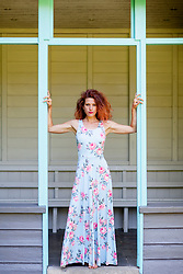 Woman in Floral Dress Standing in Gazebo Doorway