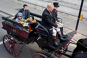 A aerial view of an excited young boy and older tourists being taken around the capital by horse-drawn carriage down Whiutehall in Westminster, on 5th June 2019, in London, England.
