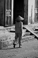 Woman wearing a conical hat walking along the old french colonial architecture that lines the Hoi An waterfront.