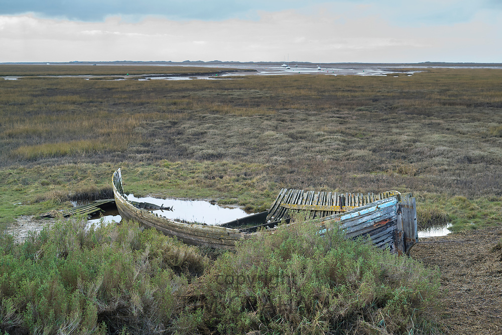 Abandoned derelict shabby sailing boat in marshland at Brancaster Staithe, Norfolk, UK