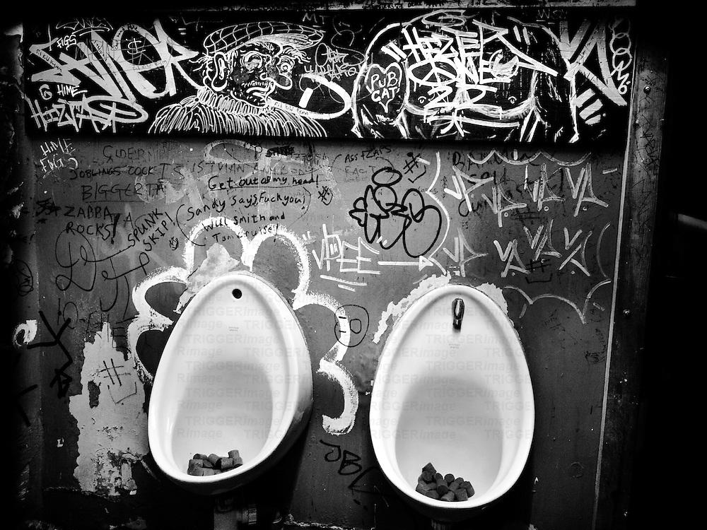 Male urinal in pub with graffiti